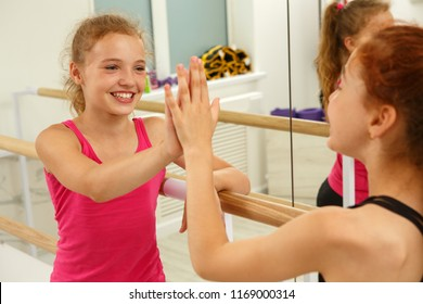 Two female  friends highing five after workout in fitness studio. Cute little girls with blonde and ginger hair happy and positive after practicing sport. Background of mirror and ballet barres.