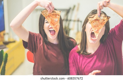 Two female friends holding pizza slices in front of their faces - Young people having fun eating dinner - Rebel concept - Focus on left slice - Warm cinematic filter