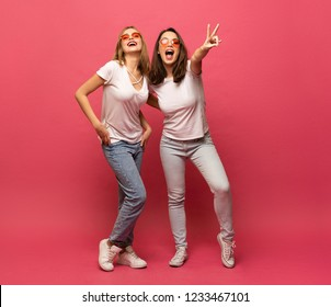 Two female friends hugging and having fun together, showing peace gesture while looking at camera, isolated over pink background