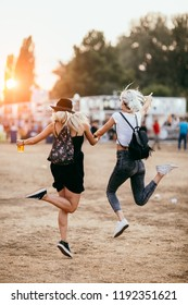Two female friends jumping and having fun at music festival. Back view