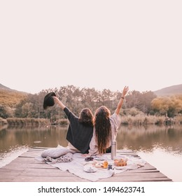 Two female friends in knitted warm sweaters having picnic near lake with autumn forest and lake on the background. Cozy fall atmosphere. Place for text.