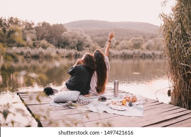 Two female friends in knitted warm sweaters having picnic near lake with autumn forest and lake on the background. Cozy fall atmosphere.