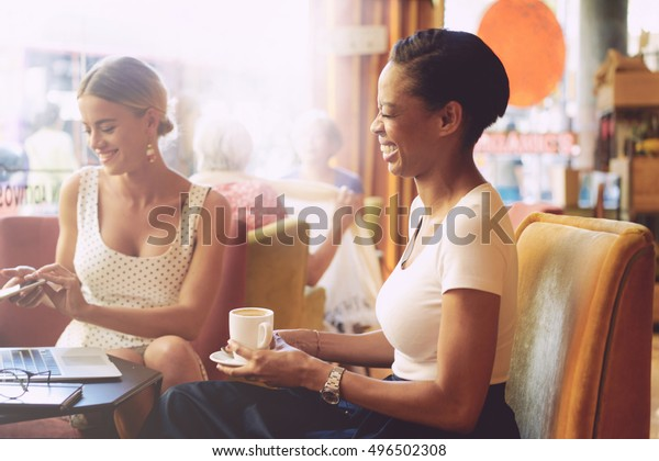 Two female friends are laughing while having rest in a coffee shop. Two cheerful  business women are discussing latest news during the informal meeting in a cafe.
