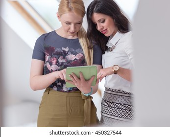 Two female friends looking at ipad. Smiling and looking happy