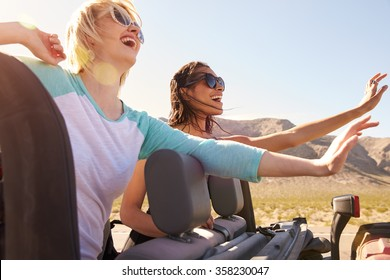 Two Female Friends On Road Trip In Back Of Convertible Car