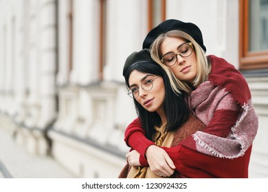 Two female friends outdoors portrait. Girls in casual warm outfits, glasses and berets sitting and hugging on urban background, copy space. City lifestyle, friendship and sisterhood concept.