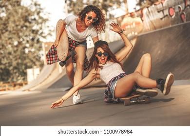 Dos amigas jugando con patineta en el parque de patinaje. Una chica empujando a otra por detrás. Riéndose y divertida.
