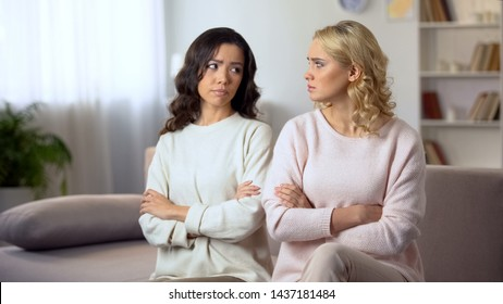 Two female friends reconciling after quarrel, sitting on sofa with friends