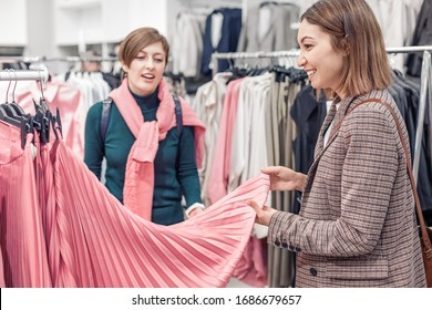 Two female friends are shopping and choosing skirt in the Mall. Lifestyle and leisure concept