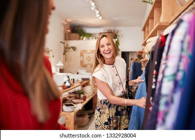 Two Female Friends Shopping In Independent Clothing Store Looking At Racks
