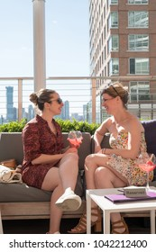 Two female friends sitting in the sun on a trendy rooftop bar in Manhattan. Two girls having a drink, relaxing at a rooftop bar on the weekend in the city. Having fun drinking on a roof.