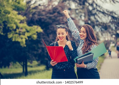 Two female friends, students celebrating success in a park - Image