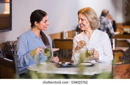 Two female friends talking at cafe table with tea and dessert and smiling