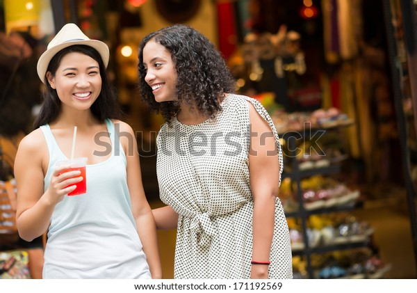 Two female friends talking and laughing in store