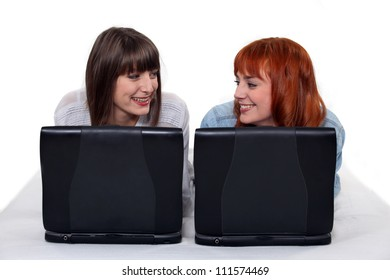 Two female friends with their laptops.