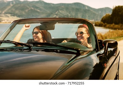 Two female friends travel in cabriolet car