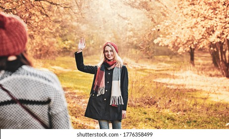 Two female friends walking in park and greeting each other while keeping social distance