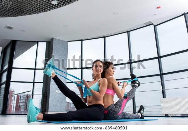 2人の女性の友人がジムで一緒に運動し、マットの上に座り、伸縮性のあるバンドで脚の筋肉を後ろに伸ばす