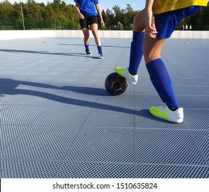 Two female futsal players in an outdoor futsal rink. Young women playing futsal, a variant of football played on hard court instead of grass or turf field. Athletic women having fun together.