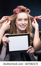 Two female hairstylists curling hair with curlers of smiling young woman showing digital tablet