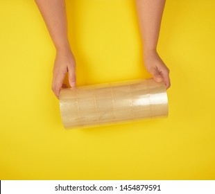 two female hands holding a stack of transparent scotch on a yellow background, adhesive tape