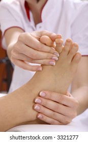 Two female hands massaging a foot