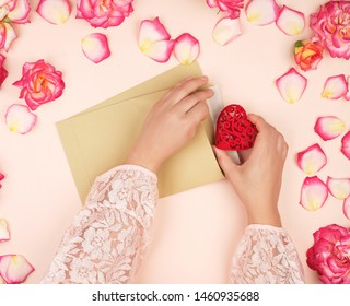 two female hands put a red heart in a brown paper envelope, the concept of congratulations on the holiday and love