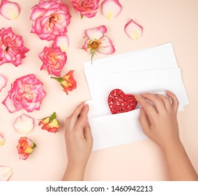 two female hands put a red heart in a white paper envelope,  concept of congratulations on the holiday and love