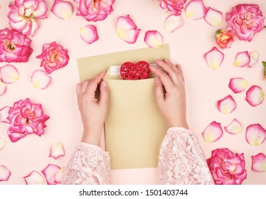 two female hands put a red heart in a brown paper envelope, concept of congratulations on the holiday and love