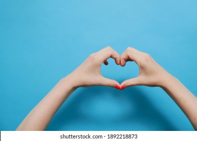 Two female hands with red gel polish manicure making heart sign isolated on blue background. Close-up and copy space.