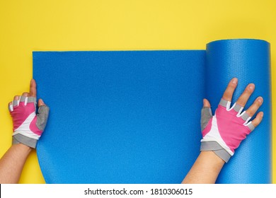 two female hands in sports gloves unfold a blue yoga mat, top view, yellow background