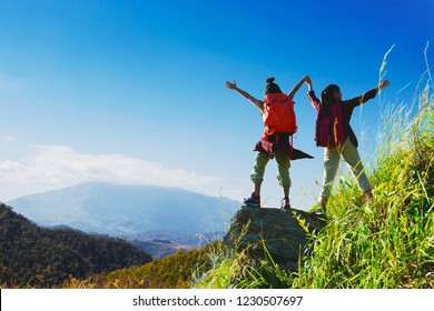 Two female hikers enjoying on the top of cliff mountian.