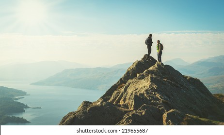Two female hikers on top of the mountain enjoying valley view, Ben A'an, Loch Katrina, Highlands, Scotland, UK