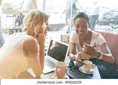 Two female hipsters are watching photos on a screen of a cell phone while having rest in a coffee shop. Two international students are sitting with electronic devices in a campus cafe during break.