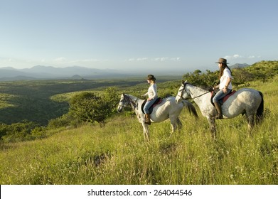 Two female horseback riders on horseback ride at sunset as one points overlooking the valley of Lewa Wildlife Conservancy in North Kenya, Africa