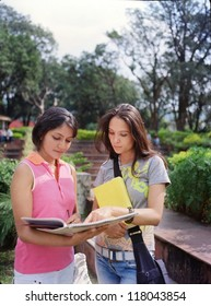 Two female Indian / Asian college students sharing notes  in the campus.
