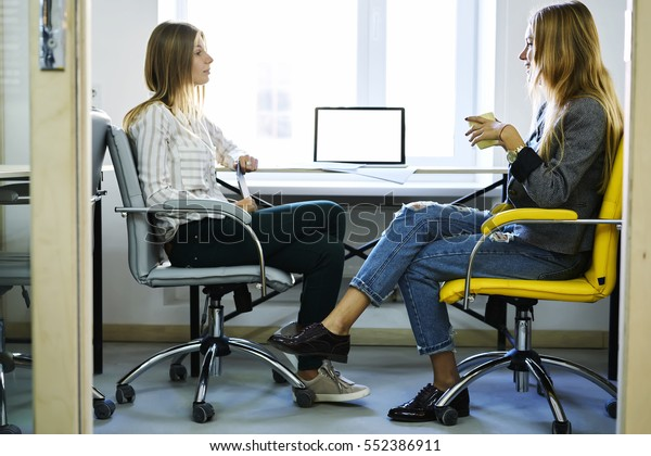 Two female journalists colleagues having friendly conversation with cup of coffee gossiping in friendly atmosphere sitting in coworking office sitting near laptop computer with mock up screen