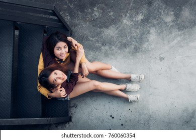Two female lesbian lgbt couple sitting at black rooftop stair  hug together and looking up at party,love wins concept,top view