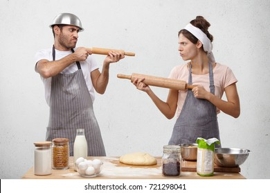 Two female and male competitors struggle for winning culinary contest, target at each other with rolling pins, have irritated and furious expressions, use kitchen supplies as weapon for defense