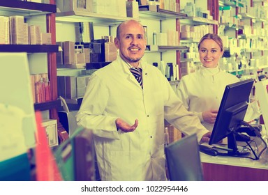 Two female and male pharmacists in white coats working the pharmaceutical store