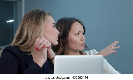 Two female managing directors discussing ideas of project while sitting on conference in office hall