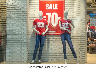 Two female mannequins in red t-shirts and blue jeans in store window on white brick wall background. Advertising 70% sale discount. Black Friday cheap clothes