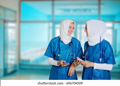 Two female middle eastern doctors in blue medical uniform standing in a hospital hallway, looking at each other, laughing while holding smart phones in their hands