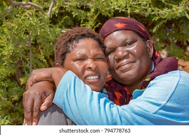 Two female models from Botswana Africa holding each other tight at cheeks in close frienship looking determined and confident and strong with arms around them