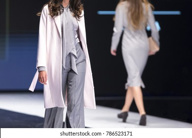 Two female models walk the runway in different dresses during a Fashion Show. Fashion catwalk event showing new collection of clothes.