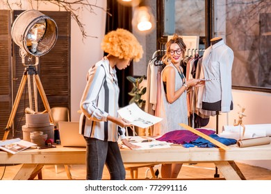 Two female multi-ethnic fashion designers working with clothes drawings standing at the office with different tailoring tools and mannequin