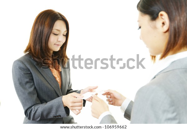 Two female office workers who change a business card each other