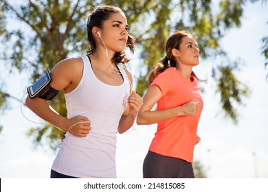 Two female runners working out while listening to music on their mobile phone on an armband