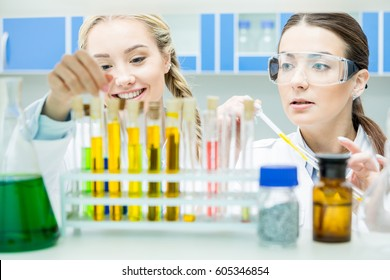 Two female scientists working with reagents in test tubes in laboratory
