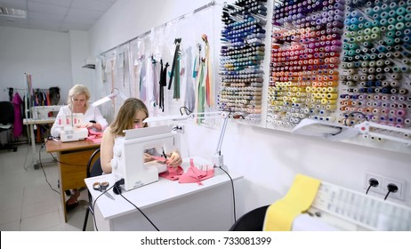 Two female seamstresses working on sewing machine sitting at the tables in tailoring studio near the wall with spools of thread.